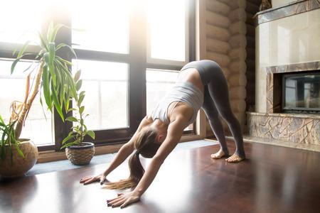 Jonge vrouw, beoefenen, yoga, staand, in, neerwaarts kijkend, hond, oefening, adho, mukha, svanasana, pose, uitwerkend, vervelend, sportkleding, grijze, broek, beha, binnen volle lengte, woning, binnenste, achtergrond Stockfoto