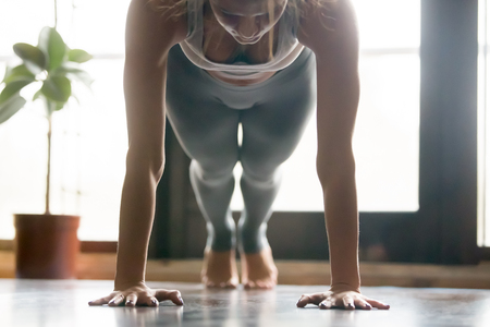 Young attractive woman practicing yoga, standing in Push ups, press ups, phalankasana exercise, Plank pose, working out, wearing sportswear, grey pants, bra, indoor, home interior background. Close up Stock Photo