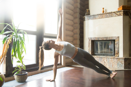 near side: Young attractive woman practicing yoga near fireplace, standing in Side Plank exercise, Vasisthasana pose, working out, wearing sportswear, grey pants, bra, indoor full length, home interior