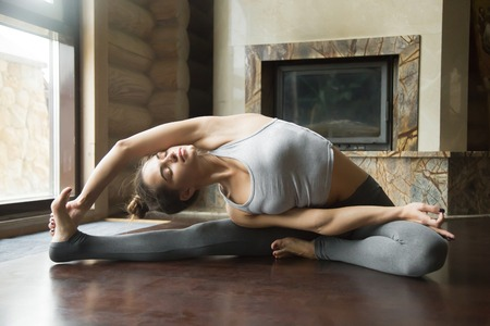 Young woman practicing yoga, sitting in Revolved Head to Knee Forward Bend exercise, Parivrtta Janu Sirsasana pose, working out, wearing sportswear, grey pants, bra, full length, home interior