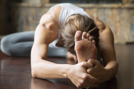 janu: Close up of young woman practicing yoga, sitting in Head to Knee Forward Bend exercise, Janu Sirsasana pose, working out, wearing sportswear, grey pants, bra, indoor, home interior background Stock Photo