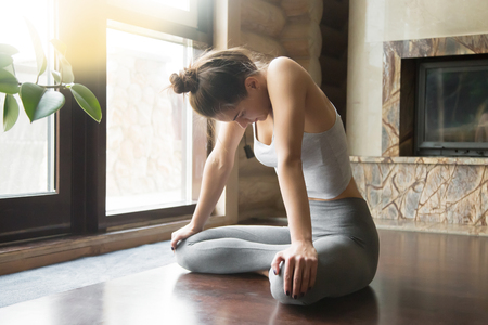 siddhasana: Young attractive woman practicing yoga, sitting in Uddiyana Bandha exercise, Upward Abdominal Lock pose, working out, wearing sportswear, grey pants, bra, indoor full length, home interior background