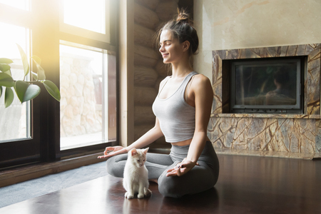 Young attractive smiling woman practicing yoga, sitting in Half Lotus exercise, Ardha Padmasana pose, working out, wearing sportswear, meditation session, indoor full length, home interior, cat near