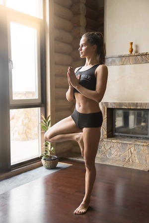 tree position: Young attractive woman practicing yoga, standing in Tree exercise, Vrksasana pose, working out, wearing sportswear, black tank top, shorts, indoor full length, home interior background, near fireplace