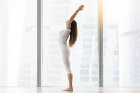 Young attractive woman practicing yoga, standing in Tadasana exercise, mountain pose, working out, wearing sportswear, white t-shirt, pants, indoor full length, near floor window with city view Stock Photo