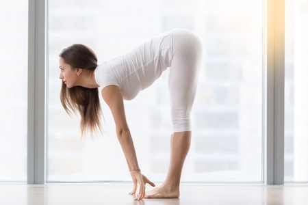 Young woman practicing yoga, standing in head to knees, Ardha uttanasana exercise, Half forward bend pose, working out, wearing sportswear, white t-shirt, pants, indoor full length, near floor window