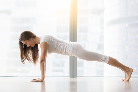 Young happy attractive woman practicing yoga, doing Push ups or press ups, phalankasana, exercise, Plank pose, working out, wearing sportswear, white t-shirt, pants, full length, near floor window