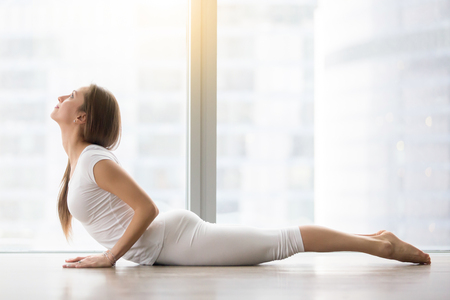 bhujangasana: Young attractive happy woman practicing yoga, doing Cobra exercise, Bhujangasana pose, working out, wearing sportswear, white t-shirt, pants, indoor full length, near floor window with city view