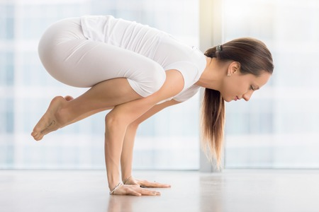 Side view portrait of young attractive woman practicing yoga, standing in Crane exercise, Bakasana pose, working out, wearing white sportswear, indoor full length, near floor window with city view