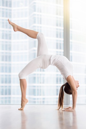 Young attractive woman practicing yoga, standing in One legged Wheel exercise, Bridge pose, working out, wearing sportswear, white t-shirt, pants, indoor full length, near floor window with city view
