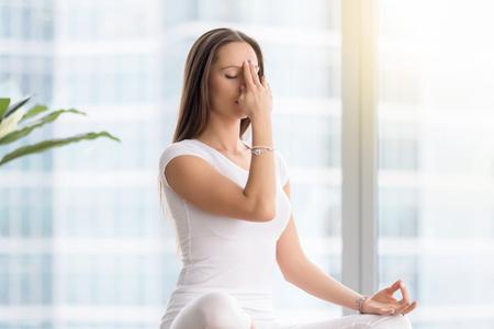 Jonge aantrekkelijke vrouw beoefenen van yoga oefening, zittend in Sukhasana pose, het uitvoeren van Alternate neusgat ademhalen techniek, nadi shodhana pranayama, het uitwerken, gekleed in witte sportkleding, indoor