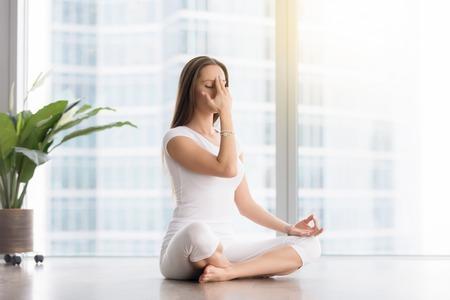 sukhasana: Young woman practicing yoga exercise, sitting in Sukhasana pose, Alternate Nostril Breathing technique, nadi shodhana pranayama, working out, wearing white sportswear, indoor full length Stock Photo