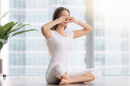 Young woman practicing yoga, sitting in Sukhasana pose, performing Humming Bee Breathing exercise, Bhramari Pranayama technique, working out, wearing sportswear, white t-shirt, pants, full length Stock fotó