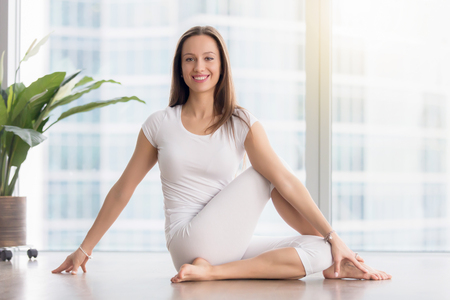 Portrait of young happy woman practicing yoga, sitting in Ardha Matsyendrasana exercise, Half lord of the fishes pose, working out, wearing white sportswear, indoor full length, looking at camera