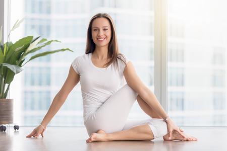 요가 연습을 젊은 행복 한 여자 Ardha Matsyendrasana 운동에 앉아의 초상화, 절반 주인 물고기, 운동, 흰색 운동복을 입고, 실내 전체 길이, 카메라를 찾고 포