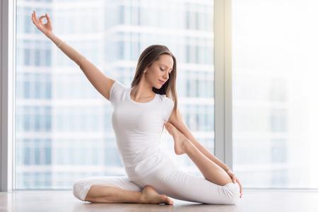animal practice: Young happy woman practicing yoga, sitting in One Legged King Pigeon exercise, Eka Pada Rajakapotasana pose, working out, wearing sportswear, white t-shirt, pants, indoor full length