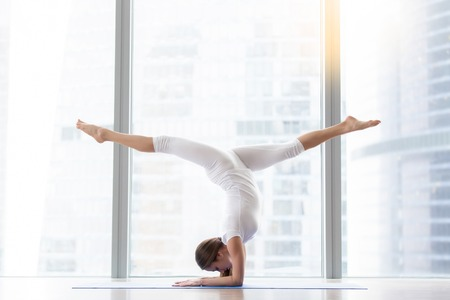 Young woman practicing yoga, standing in handstand exercise, variation of Pincha Mayurasana pose, working out, wearing white sportswear, indoor full length, floor window with city view. Copy space