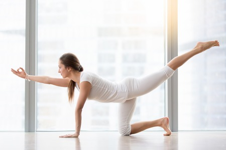 Young attractive woman practicing yoga, stretching in Bird dog exercise, Donkey, Kick pose, working out, wearing sportswear, white t-shirt, pants, indoor full length, near floor window with city view