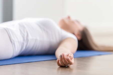 Closeup of young attractive woman practicing yoga, lying in Savasana exercise, Dead Body, Corpse pose, working out, wearing sportswear, white t-shirt, indoor, fingers in focus