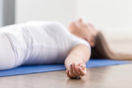haciendo ejercicio: Detalle de la joven mujer atractiva la práctica de yoga, situada en el ejercicio Savasana, cadáver, cuerpo muerto, que se resuelve, con ropa deportiva, camiseta blanca, cubiertas, dedos en el foco