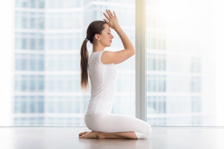 Side view portrait of young attractive woman practicing yoga, sitting in vajrasana exercise, seiza pose, working out, wearing white sportswear, indoor full length, near floor window with city view