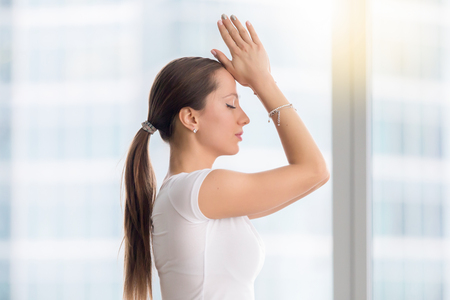 asana: Young attractive yogi model practicing yoga exercise, working out with closed eyes, wearing sportswear, white t-shirt, indoor, near window with city view, closeup Side view lifestyle portrait Stock Photo