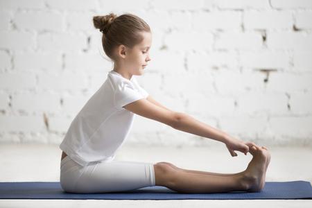 Dziewczynka ćwicząca jogę, rozciągająca się w ćwiczeniach paschimottanasana, siedząca pozycja zginania do przodu, ćwiczenia, noszenie odzieży sportowej, kryty na całej długości, białe tło studio loft Zdjęcie Seryjne