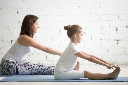 Kids yoga female teacher training a girl child, two people practicing yoga, sitting in paschimottanasana exercise, seated forward bend pose, working out wearing sportswear, indoor, white studio Stock Photo
