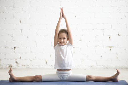 Girl child practicing yoga, doing splits, stretching in Samakonasana exercise, Straight Angle pose, working out wearing sportswear, t-shirt, pants, indoor full length, white studio background
