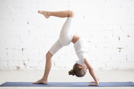 eka: Girl child practicing yoga or fitness, standing in Bridge exercise, One legged Wheel pose, working out wearing sportswear, t-shirt, pants, indoor full length, white loft studio background