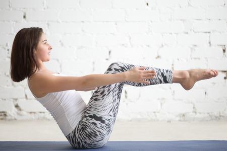 요가 연습을 젊은 매력적인 여자 보트 포즈, navasana 운동, 운동복, 위쪽, 바지, 실내 전체 길이, 흰색 로프트 스튜디오 배경 입고 밖으로 작동에 앉아 스톡 콘텐츠