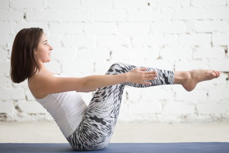 Young attractive woman practicing yoga, sitting in boat pose, navasana exercise, working out wearing sportswear, top, pants, indoor full length, white loft studio background Stok Fotoğraf - 70398710