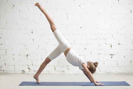 Girl child practicing yoga, standing in one legged downward facing dog exercise, eka pada adho mukha svanasana pose, working out wearing sportswear, t-shirt, pants, indoor full length, white studio