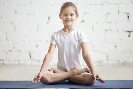 Portrait of smiling girl practicing yoga, sitting in Padmasana exercise, Lotus pose, working out wearing sportswear, indoor full length, white loft studio background. Yogi kid on meditation session