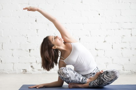 sukhasana: Young cheerful attractive woman practicing yoga, sitting in Sukhasana pose, side bend exercise, working out wearing sportswear, top, pants, indoor full length, white loft studio background