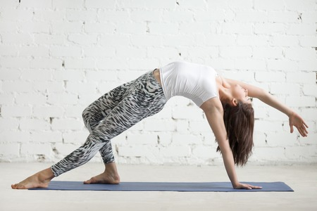 plank position: Young attractive woman practicing yoga, doing Wild Thing, Flip-the-Dog exercise, Camatkarasana pose, working out wearing sportswear, top and pants, indoor full length, white loft studio background Stock Photo