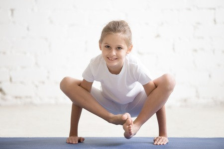 Portrait of smiling yogi girl child practicing yoga, standing in Bhuja Pidasana exercise, bhujapidasana pose working out wearing sportswear, indoor full length, white loft studio background