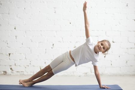 요가 연습 Vasisthasana 운동, 측면 판자 포즈, 운동복, 티셔츠, 바지, 실내 전체 길이, 흰색 스튜디오 배경 입고 밖으로 작동하는 웃는 여자 아이의 초상화