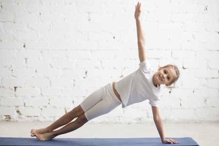 Portrait of smiling girl child practicing yoga, standing in Vasisthasana exercise, Side Plank pose, working out wearing sportswear, t-shirt, pants, indoor full length, white studio background