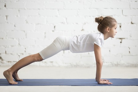 Side view of girl child practicing yoga, standing in phalankasana pose, Push ups or press ups exercise, working out wearing sportswear, t-shirt, pants, indoor full length, white loft studio background Stock Photo