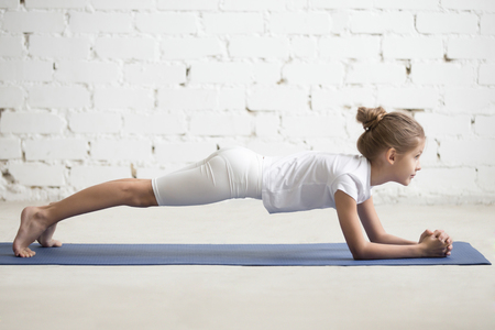 Serious girl child practicing yoga, standing in Dolphin Plank exercise, phalankasana pose working out wearing sportswear, t-shirt, pants, indoor full length, white loft studio background Stock Photo