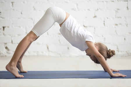 downward: Girl child practicing yoga, standing in Downward facing dog exercise, adho mukha svanasana pose, working out wearing sportswear, t-shirt, pants, indoor full length, white loft studio background