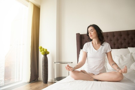 Young happy woman practicing yoga at home bedroom after waking up, sitting on unmade bed in Padmasana exercise, Half Lotus pose on meditation session, working out, wearing white casual clothes, indoor