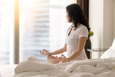 breathe easy: Young yogi woman practicing yoga after waking up, sitting in Padmasana exercise on unmade bed, Lotus pose on meditation session, working out wearing white casual clothes, looking at window. Copy space