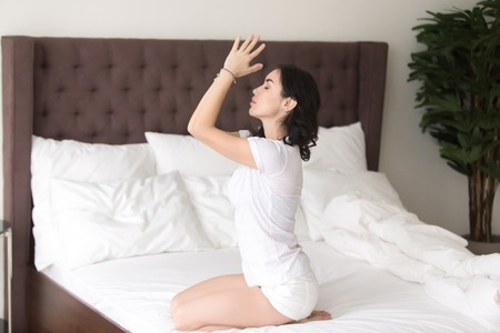 Young sporty attractive woman practicing yoga at home after waking up, sitting in seiza pose, vajrasana exercise working out wearing white casual clothes, indoor full length, hotel bedroom, unmade bed