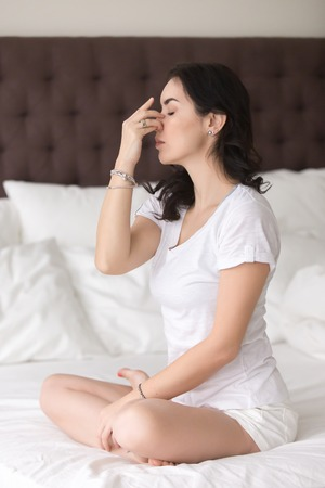 breathing exercise: Young attractive woman practicing yoga at home, sitting in Sukhasana pose, Alternate Nostril Breathing exercise, nadi shodhana pranayama, working out wearing white casual clothes, full length, bedroom