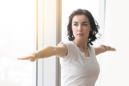 Young attractive woman practicing yoga after waking up in the morning, standing in Warrior Two exercise, Virabhadrasana II pose, working out, wearing white casual clothes, indoor, against sunny window Stock Photo