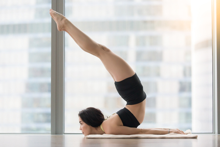 reversed: Young attractive woman practicing yoga, stretching in Reversed Locust exercise, Viparita Salabhasana pose, working out, wearing sportswear, black tank top, shorts, indoor full length, floor window
