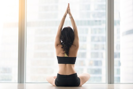 siddhasana: Rear view of woman practicing yoga, sitting in Padmasana exercise, Lotus pose, working out, wearing black sportswear, indoor full length, meditation session in the morning, floor window, back view