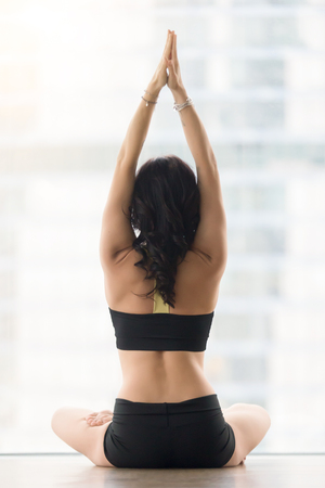 Rear view of woman practicing yoga, sitting in Ardha Padmasana exercise, Half Lotus pose, working out, wearing sportswear, black tank top, shorts, indoor full length, against floor window, back view